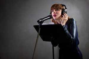 professional female voiceover artist with headphones and microphone